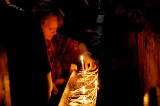 A Pilgrim lights candles outside of the tomb.