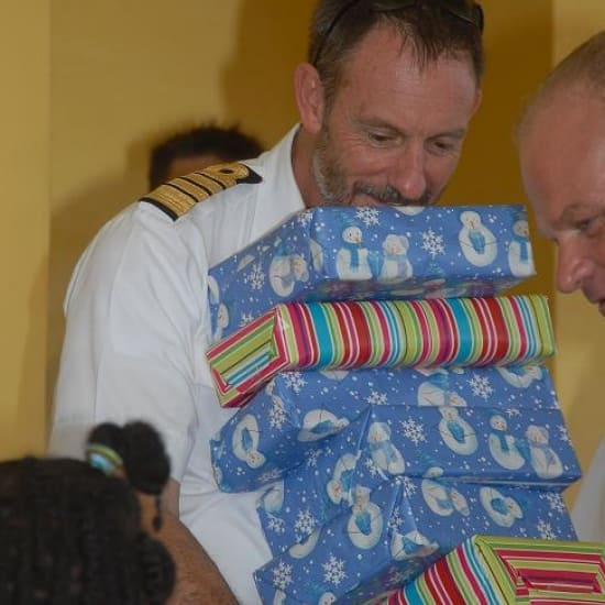 Zuiderdam's Captain Turner delivering presents to the children of Curacao.