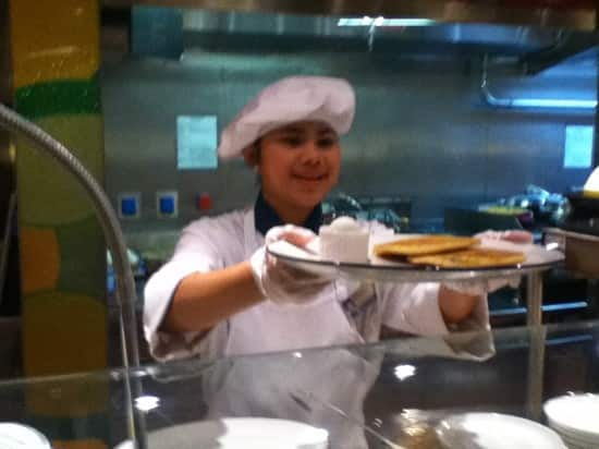 Lido Restaurant server Dini with a made-to-order plate of blueberry pancakes.