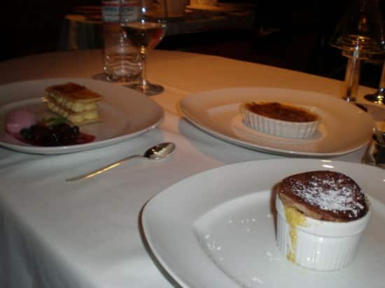 Trio of desserts: Chocolate Souffle, Crème Brulee Le Cirque, and Napoleon pastry with berry compote.