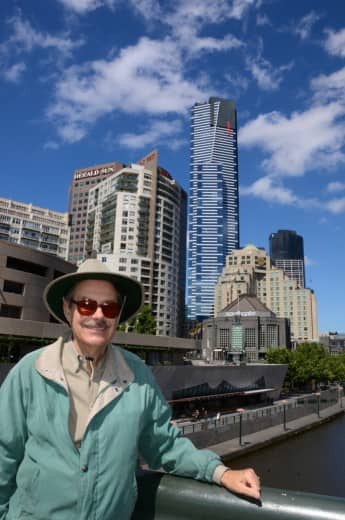 Al on bridge over the Yarra River with the skyline of Melbourne behind him