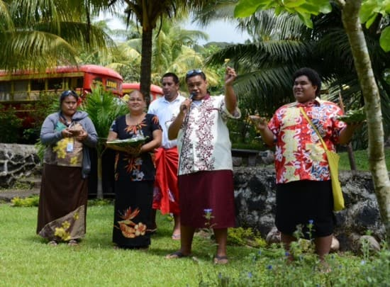 Samoans at the cultural center with pieces of banana for us to dip into the coconut milk. Note the Island Buses in the background