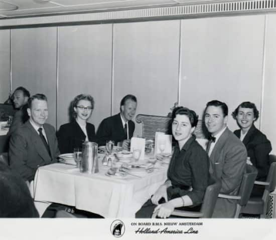 Dorothy Goldman is seated in the middle on the left side of the table in the dining room.