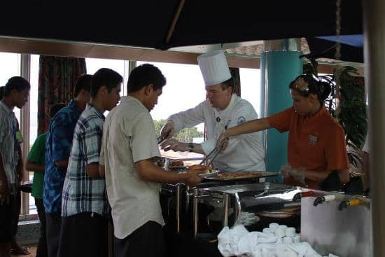 From left: Oosterdam Second Executive Chef Norbert Sommerhalter and the ship's Lido Assistant Steward Indaharini Nenobais serve children food on board.