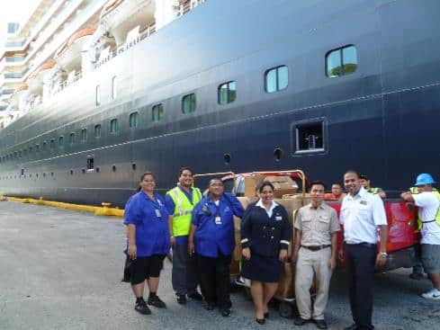 From lef: Ship'ss agent (name) on behalf of  the American Samoa Red Cross, Oosterdam Human Resources Manager Natalie Ansari and Housekeeping (role/name?).