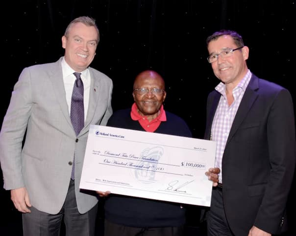 Archbishop Tutu accepting Holland America Line's donation with Kruse, left, and NAME.