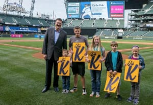 HAL Executive Vice President Sales, Marketing & Guest Programs Rick Meadows, with (from left) Eddie, who was a patient at Seattle Children's, Isaac, Lucy, Ian and Eva Harper during a ceremony at Safeco Field May 29.