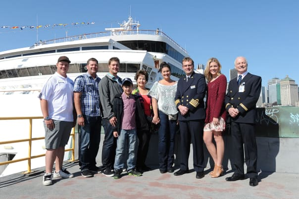 Marianne Visser, the 100,000 passenger to disembark in Montréal, surrounded by her family, Captain Smit and Port of Montréal representatives. (Photo courtesy CNW Group/Tourisme Montréal)
