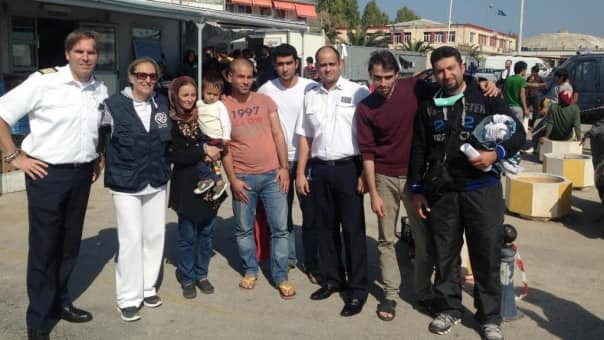 Hotel Director Marco van Belleghem, far left, and Assistant Housekeeper Savio DSilva, third from right, with a rescue worker and refugees in Mytilene.