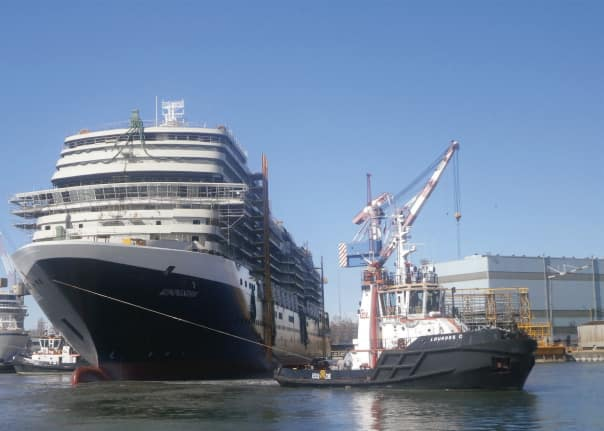 Koningsdam moving to the outfitting dock with the assistance of a tug.