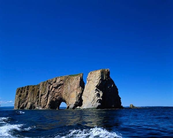 Perce Rock rises from the ocean along Canada's coastline.