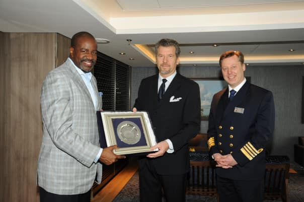 Holland America Line President Orlando Ashford and Captain Emile de Vries accept a gift from a port official.