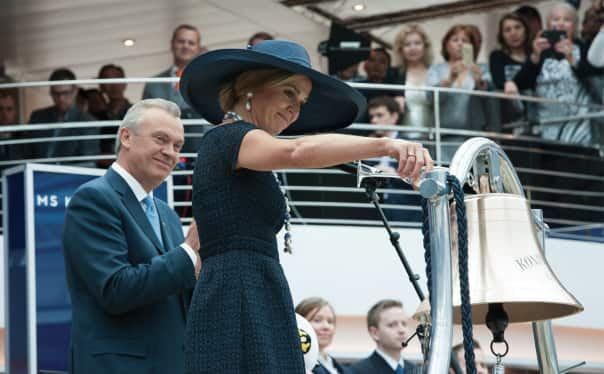 Her Majesty Queen Máxima performing the blessing the ship's bell as Stein Kruse, Holland America Group CEO, looks on.