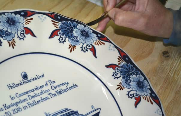 A painter perfects the final details of the Royal Goedewaagen plate created for Koningsdam's dedication.