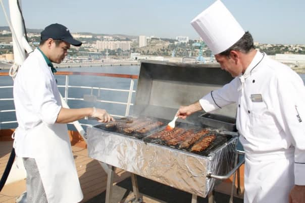 Crew members preparing ribs for guests during a shipboard barbecue.