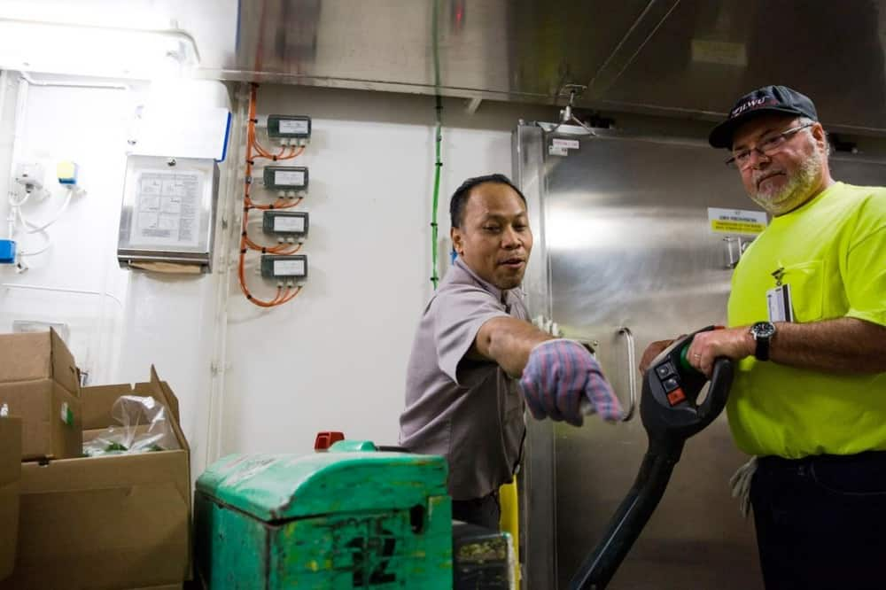Herman Hermawan works on the storage and delivery of some of the 350,000 pounds of food, beverages and supplies the ship will use during its next cruise on turnaround day. (Rebekah Welch / The Seattle Times)