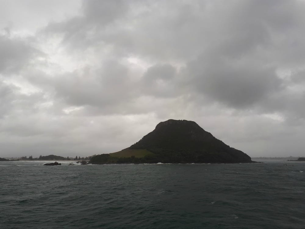 Cloudy skies greeted us on entrance to port of Tauranga. Mount Maunganui, or Mauao, is an extinct volcanic cone at the end of a peninsula and the town of Mount Maunganui in the Bay of Plenty. Photo: Kristy King ©