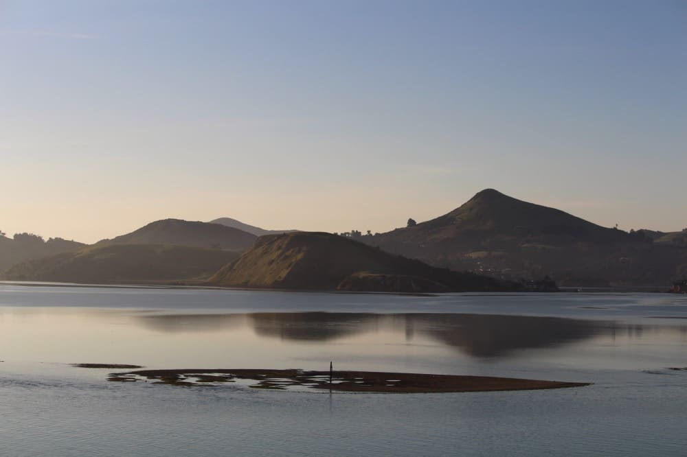Early morning light over the Otago Peninsula on entrance into Port Chalmers, New Zealand. Photo: Kristy King ©