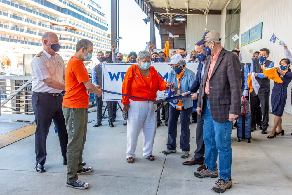Guests Sharon and Derek (orange) and Nancy and Charles cut the ribbon to open embarkation.