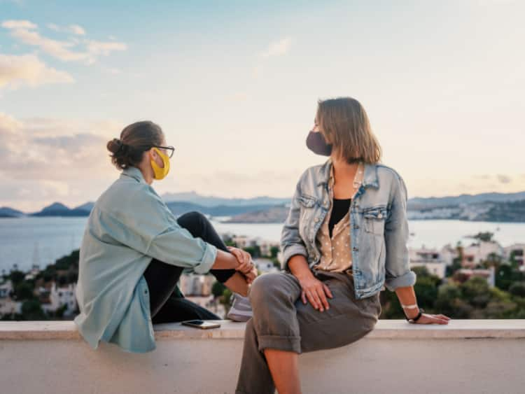 two women wearing masks while watching the sunset