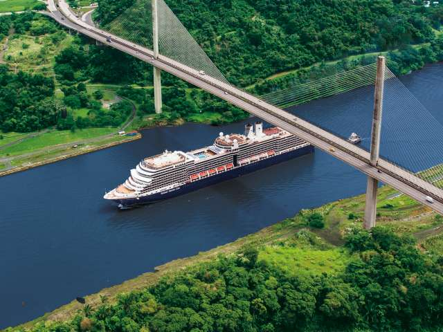Aerial view of a Holland America cruise ship sailing under a bride in the Panama Canal while on a Holiday Cruise