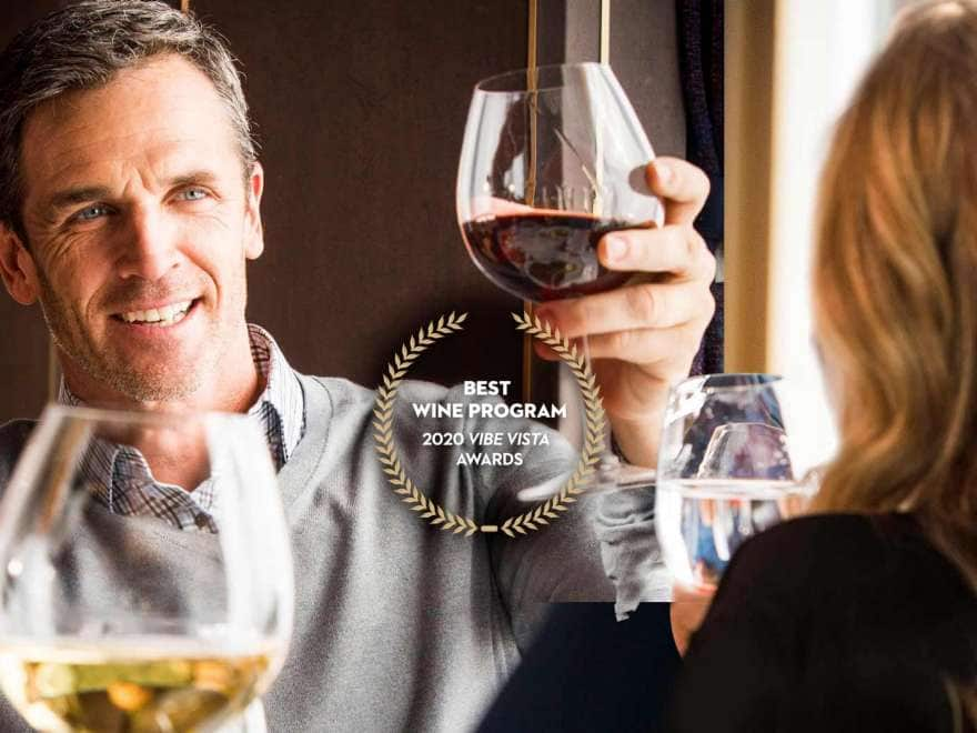 "a couple toasts with red wine, text overlay reads ""best wine program 2020 vibe vista awards"""