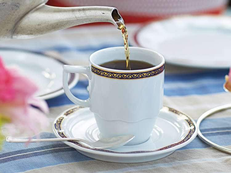 Tea pouring from teapot into cup