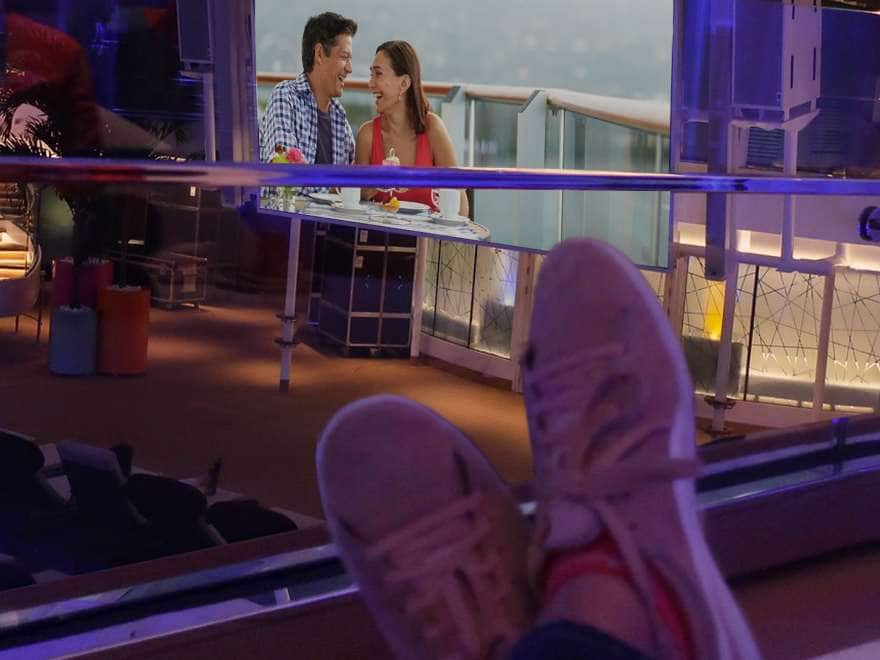 person watching movie on deck at night