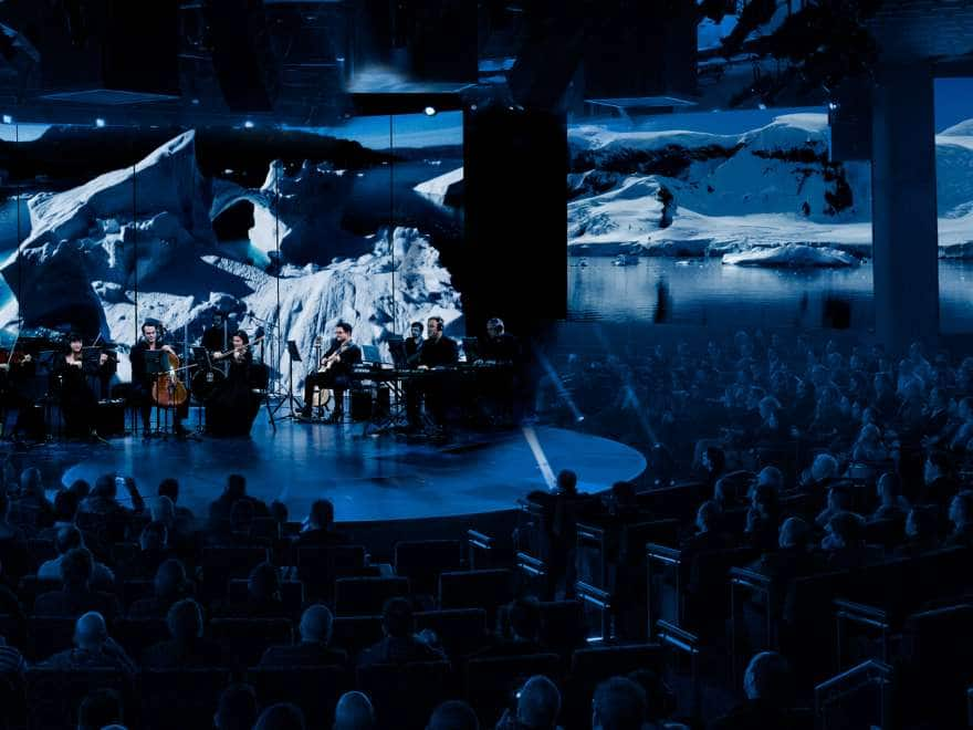 Musicians and singers performing on a round stage in front of a glacier backdrop