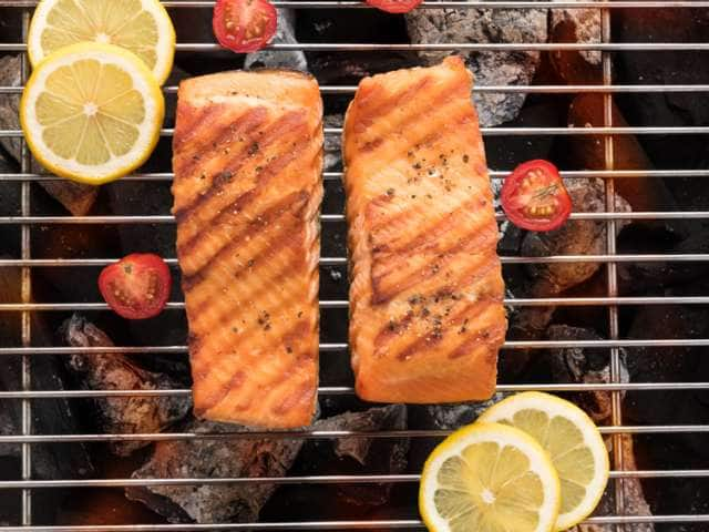 Salmon with sliced tomatoes and lemon over a grill on an Alaska cruise