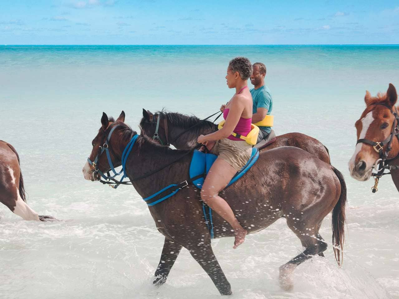 People horseback riding in the surf on Half Moon Cay, Holland America's award-winning private island