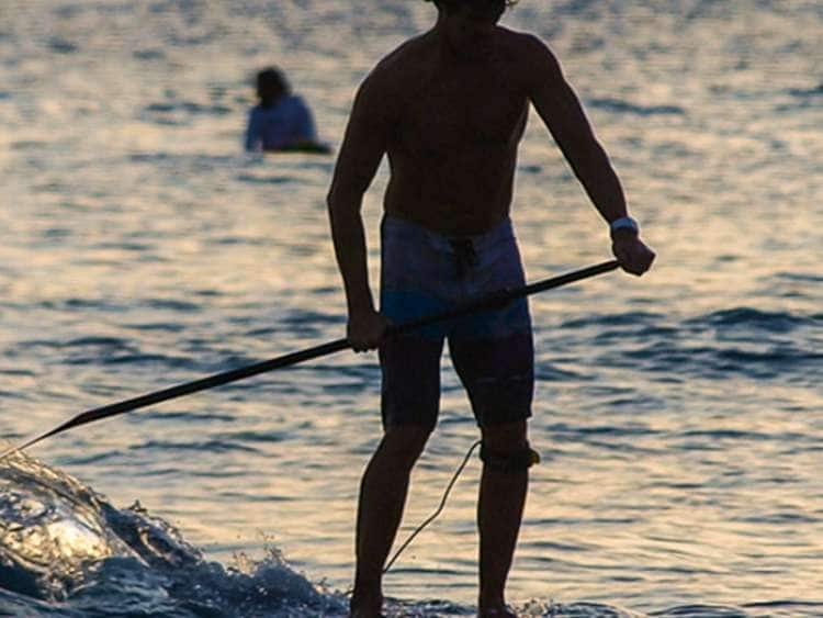 Man paddle boarding in Honolulu, Hawaii on a Hawaii cruise