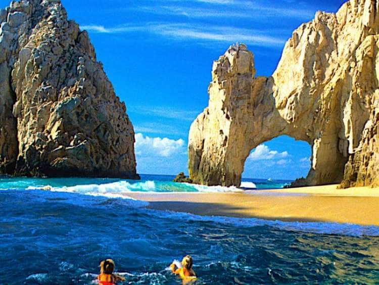 View of two people swimming on a beach in Cabo San Lucas while on a Mexico cruise