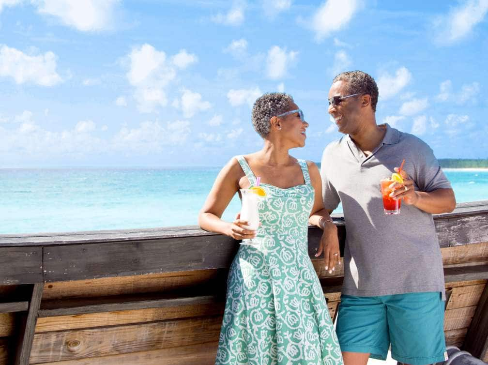View of a couple enjoying drinks with a beach in the background while on a Caribbean cruise