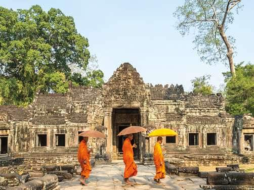View of three Buddhist monks walking in front of an old temple seen on a world cruise
