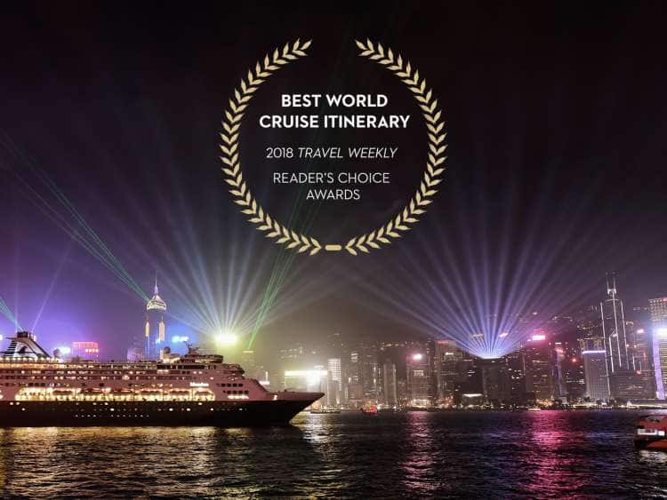 A nightly view of a Holland America Cruise Line ship pulling into Singapore on a world cruise with awards logo reading, Reader's Choice 2018 Travel Weekly Best World Cruise Itinerary.