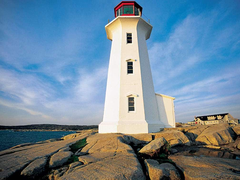 A lighthouse overlooking Peggys Cove in Nova Scotia Canada seen while on a Canada and New England cruise deal