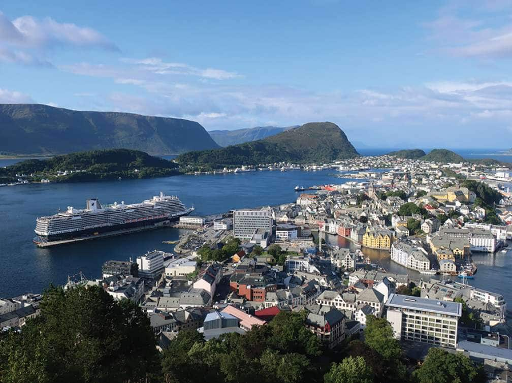 A Europe cruise deal shows an aerial view of a Holland America Cruise ship docked in Allesund, Norway