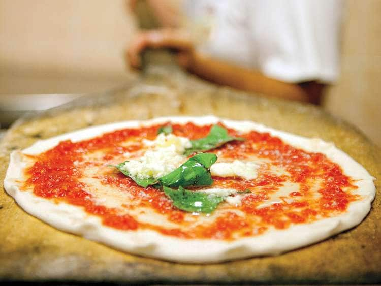 A cheese pizza with basil on top on a Europe cruise